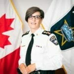 Chief Kimberly Greenwood in front of the Canadian Flag and the BPS Flag