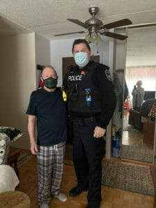 Sgt. John Parcells stands with the man whose life he saved in December 2020. Both are wearing masks due to COVID restrictions